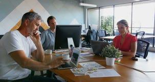 Ledare som arbetar på skrivbordet i kontoret 4k arkivfilmer
