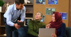 Ledare som diskuterar över bärbara datorn och den digitala minnestavlan 4k stock video