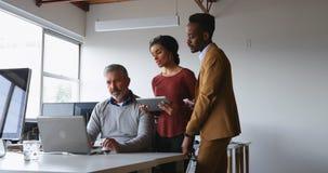 Ledare som diskuterar över bärbara datorn på skrivbordet 4k arkivfilmer