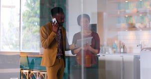 Ledare som diskuterar över den digitala minnestavlan, medan tala på mobiltelefonen 4k stock video