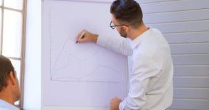 Ledare som diskuterar över whiteboard i konferensrum 4k arkivfilmer