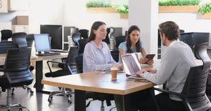 Ledare som diskuterar med de, medan genom att använda bärbara datorn 4k lager videofilmer