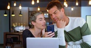 Ledare som diskuterar på mobiltelefonen i kafét 4k arkivfilmer