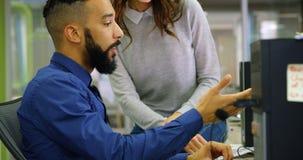 Ledare som diskuterar på skrivbords- PC på skrivbordet 4k arkivfilmer