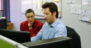 Ledare som diskuterar på skrivbords- PC på skrivbordet 4k stock video
