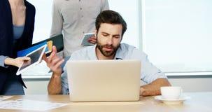 Ledare som får frustrerad, medan arbeta på hans skrivbord lager videofilmer