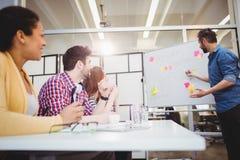 Ledare som förklarar strategi från whiteboard under idékläckning på det idérika kontoret royaltyfri foto