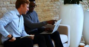 Ledare som i regeringsställning diskuterar över bärbara datorn lager videofilmer