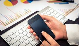 Ledare som kontaktar hans affärslag med smartphonen Fotografering för Bildbyråer