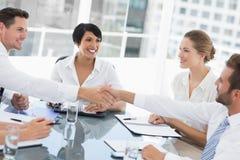 Ledare som skakar händer under ett affärsmöte Arkivbild