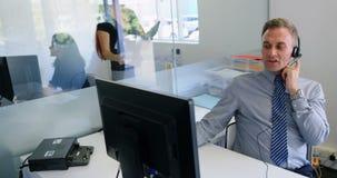 Ledare som talar på hörlurar med mikrofon, medan arbeta på datoren 4k arkivfilmer