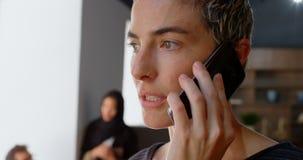 Ledare som talar på mobiltelefonen medan kollega som diskuterar i bakgrund 4k lager videofilmer