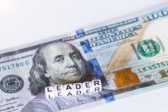 LEDAREord med vitbokstäver bland kontant dollarsedel på trävit bakgrund Kopieringsspase Stängt upp Begrepp av individen Arkivbild