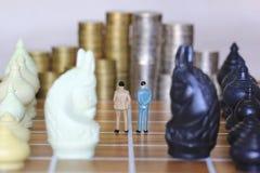 Ledarskap för framgånglek, miniatyraffärsmananseende på schackbrädet och schack med bunten av myntpengarbakgrund, strategi arkivfoton