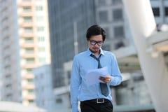Ledarskapaffärsidé Stående av den säkra unga asiatiska affärsmannen som går och ser diagram eller dokumentmappen på hans hand Arkivbild