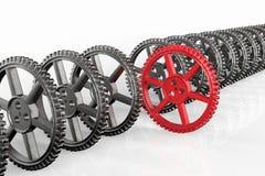 Ledarskapbegrepp med röda kugghjul- och metallkugghjul Arkivbild