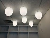 LEDDE vita krämiga ballonger som bränner flugan bort i himlen på natten i kontorsrummet med vit wood hyllabakgrund för suddighet, arkivbilder