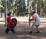 Leden van de jaarlijkse wederopbouw van het leven van de Vikingen - ` Viking Village ` toont een strijd op spears in het bos dich Royalty-vrije Stock Afbeeldingen