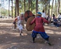 Leden van de jaarlijkse wederopbouw van het leven van de Vikingen - ` Viking Village ` toont een strijd op spears in het bos dich Stock Foto's