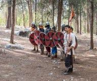 Leden van de jaarlijkse wederopbouw van het leven van de Vikingen - ` Viking Village ` toont gevechtsvorming dichtbij in het bos  Stock Fotografie