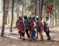 Leden van de jaarlijkse wederopbouw van het leven van de Vikingen - ` Viking Village ` toont te voet beweging in het bos aan dich Stock Afbeelding