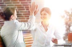Leden van het commerciële team die elkaar een hoogte vijf geven Stock Foto