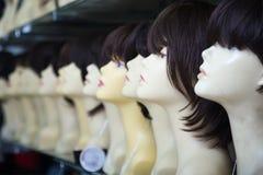 Ledenpoppen met pruiken verschillende kleuren op planken van haarsalon Stock Foto