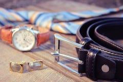 Ledergürtel, Bindung, Manschettenknöpfe und Uhren auf dem alten hölzernen Hintergrund Stockbild
