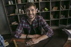 Lederhersteller des jungen Mannes, der am Holztisch mit Werkzeugen lächelt und sitzt Stockfotografie