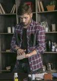 Lederhersteller des jungen Mannes verpackte in der handgemachten Geldbörse des kleinen Pappschachtelleders Stockfotografie
