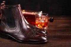 Lederne Chelsea Stiefel Browns poliert mit dem Glas- und Flaschenwhisky defocused Selektiver Fokus Einwachsen von Stiefeln Kopier stockbilder