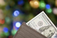 Lederne Geldbörse mit 100 Dollarscheinen über buntem Hintergrund Stockfotografie