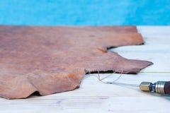 Lederne Handwerkswerkzeuge auf einem hölzernen Hintergrund Lederner craftmans Arbeitsschreibtisch Stück Fell und arbeitende handg Stockbild