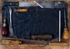 Lederne Handwerkswerkzeuge auf hölzernem Hintergrund Craftmans-Arbeitsschreibtisch Stück Fell und handgemachte Werkzeuge Beschnei Lizenzfreie Stockfotografie