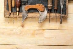 Lederne Handwerkswerkzeuge auf hölzernem Hintergrund Craftmans-Arbeitsschreibtisch Stück Fell und handgemachte Werkzeuge Beschnei Stockfoto