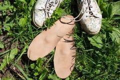 Lederne orthopädische Einlegesohlen mit Laufschuhen auf dem Gras heal lizenzfreies stockbild