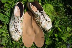 Lederne orthopädische Einlegesohlen mit Laufschuhen auf dem Gras heal stockfotografie