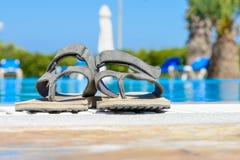 Lederne Sandalen sind am Rand des Swimmingpools Lizenzfreie Stockbilder