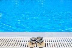 Lederne Sandalen sind am Rand des Swimmingpools Lizenzfreie Stockfotos