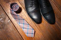 Lederne Schuhe und eine karierte Bindung Stockbilder