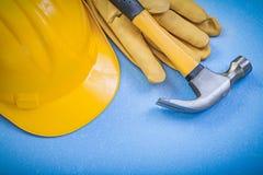 Lederne Schutzhandschuhe des Tischlerhammers, die Sturzhelm auf blauem Ba errichten Lizenzfreies Stockfoto
