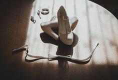 Lederne weiße Hochzeitsschuhe der hohen Absätze auf dem hölzernen Hintergrund in den Sonnenstrahlen Modeschmuckohrringe und -armb stockfoto