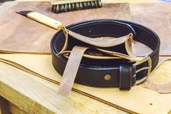 Lederne Werkstatt und Werkzeuge mit Abschluss des schwarzen Gürtels oben Lizenzfreie Stockbilder