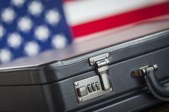 Lederner Aktenkoffer, der auf Tabelle mit amerikanischer Flagge hinten stillsteht Stockfoto