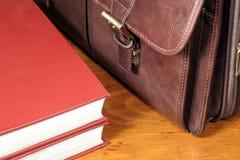 Lederner Aktenkoffer und rote Bücher Lizenzfreies Stockbild
