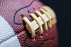 Lederner amerikanischer Fußball auf schwarzem Hintergrund Stockfotos
