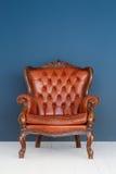Lederner brauner Luxuslehnsessel der Weinlese klassisches Brown-Ledersofa und alter blauer Hintergrund Lizenzfreie Stockbilder