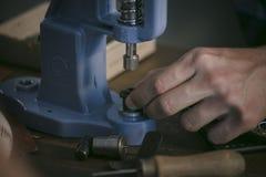 Lederner Hersteller, der mit Berufshandpresse auf Holztisch arbeitet Stockfoto