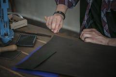 Lederner Hersteller, der mit Werkzeug auf Holztisch mit Leder arbeitet Stockfotografie