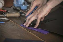 Lederner Hersteller schnitt Leder mit Gebrauchsmesser auf speziellem Stand Lizenzfreies Stockbild